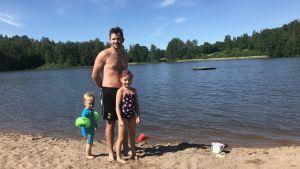 Robert Kristén står på stranden tillsammans med sina barn Freya och Elton.