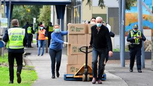 Förnödenheter levereras till invånare i ett bostadskomplex som har isolerats på grund av stora mängder coronasmittor bland invånarna.