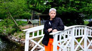 Susanna Koskinen på en vit gångbro vid ankdammen i Kuppisparken.