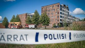 Polistejp syns suddigt i förgrunden. I bakgrunden syns byggnad där det brunnit och övriga byggnader.