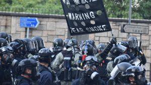 Poliser i svarta kläder och hjälmar håller i en skylt som varnar för tårgas