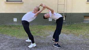 Två flickor gör en akrobatisk rörelse.