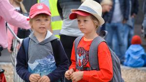 Närbild på Viljam och Vincent Westerlund. De har skolväskorna på ryggen och står ute på skolgården. De ser lite fundersamma ut.