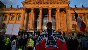 Demonstranter står framför riksdagshuset i Berlin.