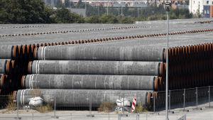 Stora gasrör staplade på varandra i en hamn.