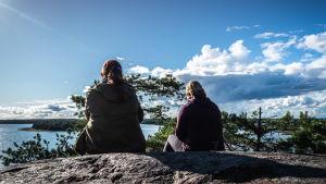 Kaksi naista istuu korkealla kalliolla ja katselee kohti merta maisemaa.