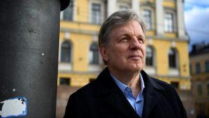En gråhårig Esko Aho står på Senatstorget framför Statsrådsborgen.