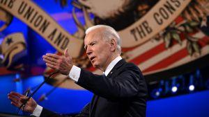En man talar vid ett podium.