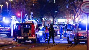 Bild på polisbilar med blåljus på. Ett stort pådrag pågår och polis och räddningspersonal står på gatan i centrala Wien.