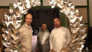 Tre män tittar fram bakom en lagerkrans.