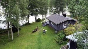 En grå sommarstuga med en kajak på den gröna gräsmattan vid en sjö.