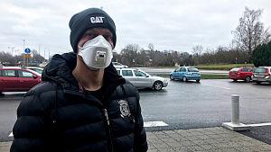 Man med munskydd vid parkering.