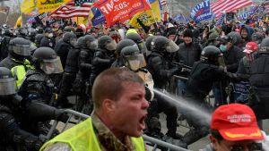 Poliser i kravallutrustning mitt i oroligheter.