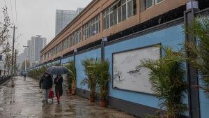 En lång tvåvåningsbyggnad med ljusblå skivor som avspärrning. Några människor promenerar förbi i regnet.