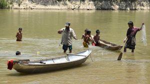 Fiskare och barn står i en flod.