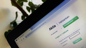 Aktias nätbankssida är öppen på en bärbar dator. I bakgrunden en grönväxt.