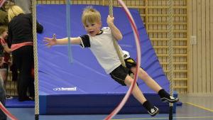 Barn hänger i rep i gymnastiksal.
