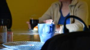 En kaffemugg och smulor på ett fat. I bakgrunden sitter en person och njuter av kaffe och bulla.