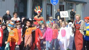 Elever går i parad på Köpmansgatan i Karis.
