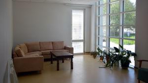 En soffa står i ett rum med stora fönster.