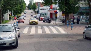 En bil kör framför ett övergångsställe på en gata.