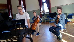 Felix Lönnqvist sitter vid en flygel, Daniel Shultz sitter med en cello och Albert Sahlström sitter med en violin i famnen.