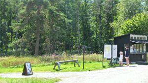 Turister läser skylt vid Raseborgs slottsruiner.