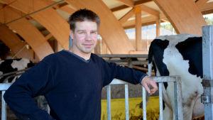 Magnus Österlund står i en ladugård. I högra hörnet syns en ko.