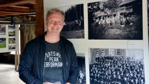 Historiker Kim Björklund står vid fyra svartvita bilder som visar arbetare i Billnäs bruk.