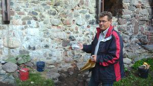Museichef Dan Lindholm visar upp en kantbit från ett gammalt pottkakel och örat från en gammal gryta.