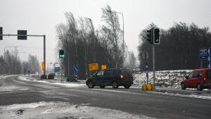 En bil kör till vänster i en korsning med trafikljus.