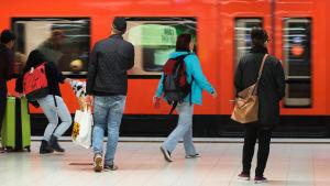 Ihmisiä astumassa metrojunaan, metro Rautatieasema