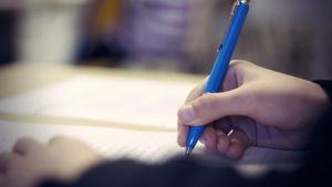 En hand som skriver med penna på ett papper