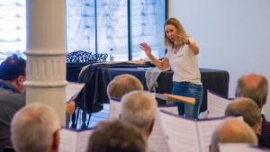 Dirigent Hanna Kronqvist leder en grupp manliga sångare.
