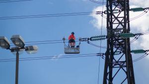 En elektriker är uppe på en högspänningslinje