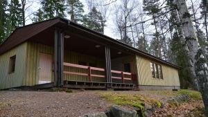 Brungrått hus med liten veranda. Vid skogsbrynet