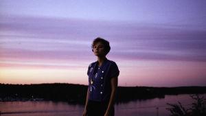 Porträttbild på Iiris Vljanen i öppet landskap  gryningsljus i rosa och lila