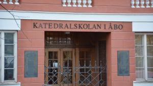 Ingången till Katedralskolan i Åbo. Byggnaden är röd med trädörrar och en järngrind.