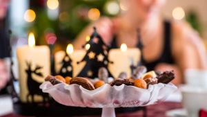 Levande ljus och ett kakfat med julgodis på ett bord framför en julgran.