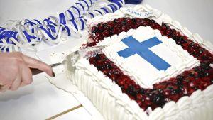 En Finland100-kaka skärs upp.