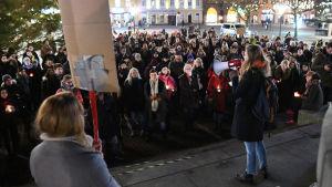 Några hundra personer demonstrerar på ett torg. I förgrunden kvinna med plakat och kvinna med megafon.
