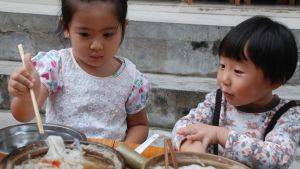 Kinesiska barn äter med pinnar