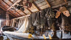 Granösundin saaristolaismuseon sisäpuolelta otettu kuva jossa näkyy vanha soutuvene ja kalaverkkoja.