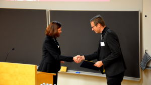 Minna Arve skakar hand och överräcker en donation till Åbo Akademi som här representeras av Niklas Sandler