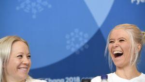 Kaisa Mäkäräinen och Mari Laukkanen skrattar på presskonferens.