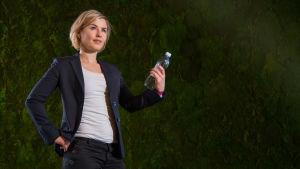 Toimittaja Päivikki Koskinen pitää mietteliäänä muovipulloa kädessään.