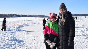 En dotter och hennes mor står vid en sjö som är isklädd. De ler och har på sig vinterkläder.
