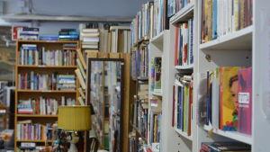 En bild på mängder avfärgglada böcker i bokhyllor.