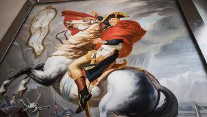 Taulu Ted Walliinista Napoleonin vaatetus yllään ratsastaen valkoisella hevosella.