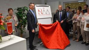 ÅA:s rektor Mikko Hupa och yrkeshögskolan Novias rektor Örjan Andersson avtäcker den nya logon.